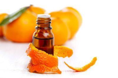 Эфирное масло мандарина в бутылочке на фоне мандаринов