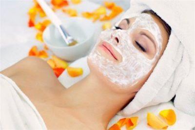 Косметическая маска с мандариновым маслом на лице женщины